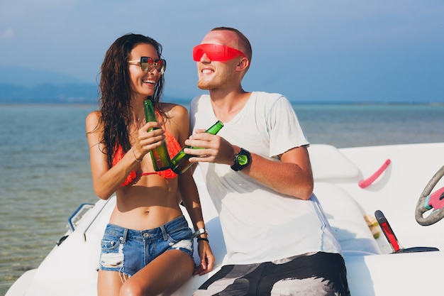 Happy hipster woman and man drinking beer on summer tropical vacation in thailand traveling on boat in sea, party on beach, people having fun together, positive emotions Free Photo