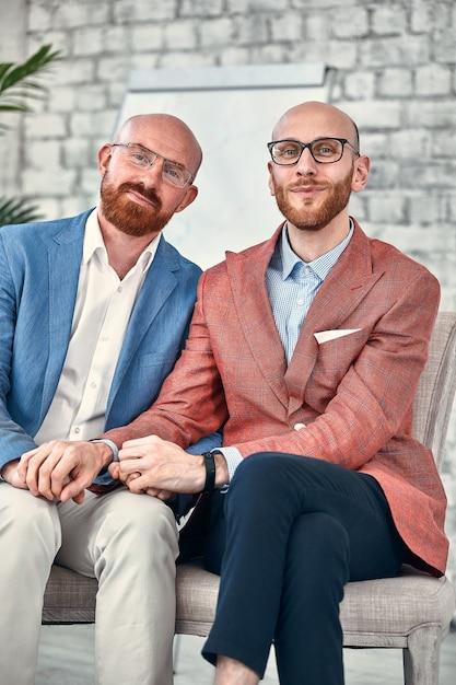 Счастливая гомосексуальная пара в офисе. гомосексуальная пара показывает миру свою чистую любовь и дружбу. Premium Фотографии