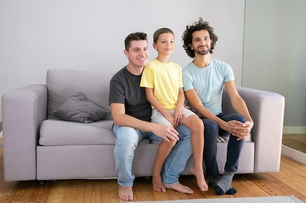 Padri omosessuali felici e bambino seduto sul divano a casa, sorridente e distogliere lo sguardo. copia spazio. famiglia e concetto di genitorialità Foto Gratuite