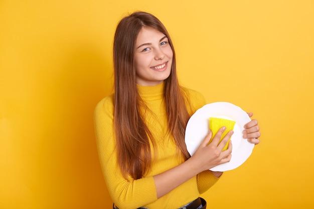 Счастливая домохозяйка демонстрирует процесс стирки, держа в руках белую тарелку и губку и в повседневной одежде Бесплатные Фотографии