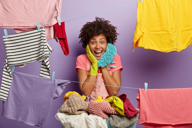 Happy housewoman hangs clean laundry on clothes line, does washing at home, busy with household duties holds mop, wears t shirt and rubber gloves, dries clothes, pegs out washing, smiles broadly Free Photo
