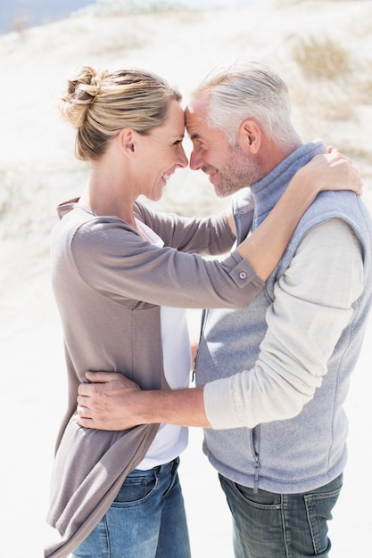 Happy hugging couple on the beach looking at each other Premium Photo
