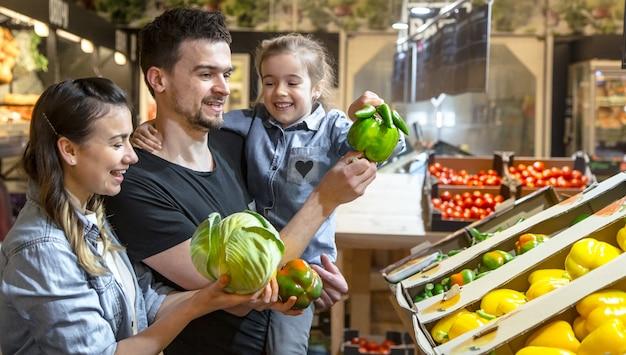 子供を持つ幸せな夫と妻は野菜を買います。スーパーマーケットや市場の野菜部門でピーマンとグリーンを選択する3人の陽気な家族。 無料写真