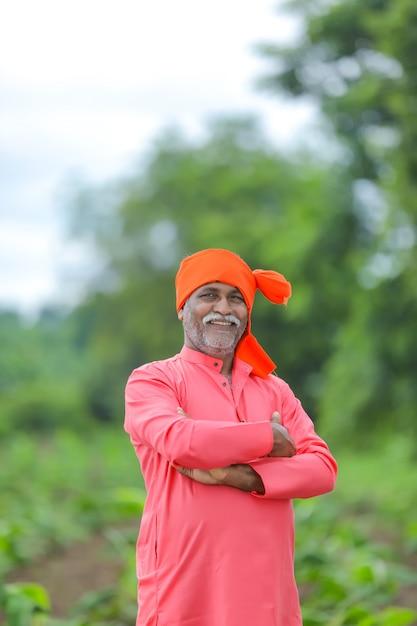 立っている幸せなインドの農民とフィールドで笑顔 Premium写真