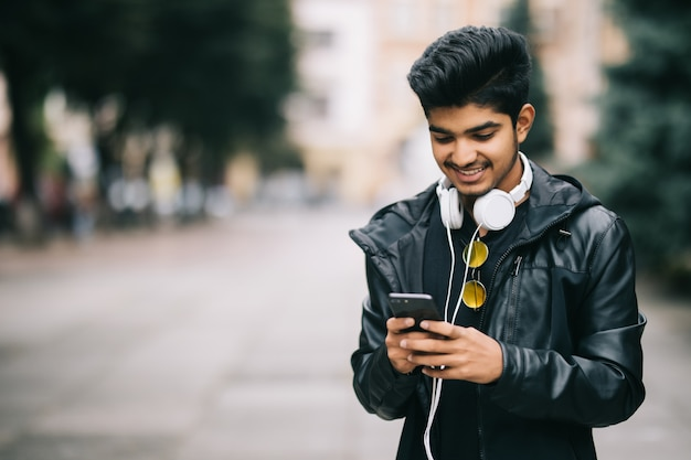 Happy indian man walking and using a smart phone to listen music with headphones Free Photo