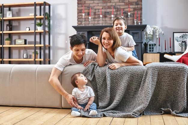 Концепция счастливой международной семьи. папа, мама, сын и маленькая дочка позируют для домашнего фотоаппарата, занимаются домашним воспитанием. домашние каникулы, воспитание детей, концепция детей и родителей. Premium Фотографии