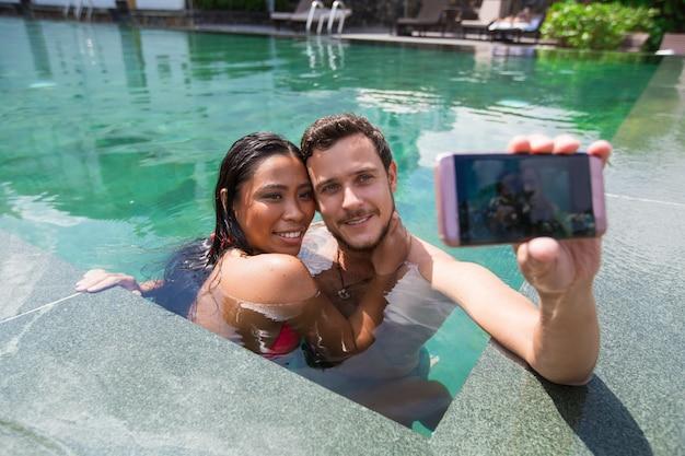 Happy Interracial Couple Taking Selfie In Pool Photo -4428