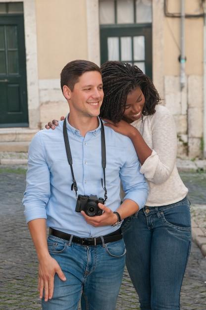 Happy interracial couple walking in city Free Photo