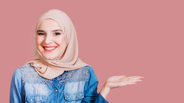Happy islamic woman presenting something on background Free Photo