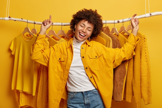 Happy joyful afro woman dances with triumph against clothes rack, prefers outfits of yellow colour, wears fashionable jacket and jeans, moves actively near home wardrobe. Free Photo