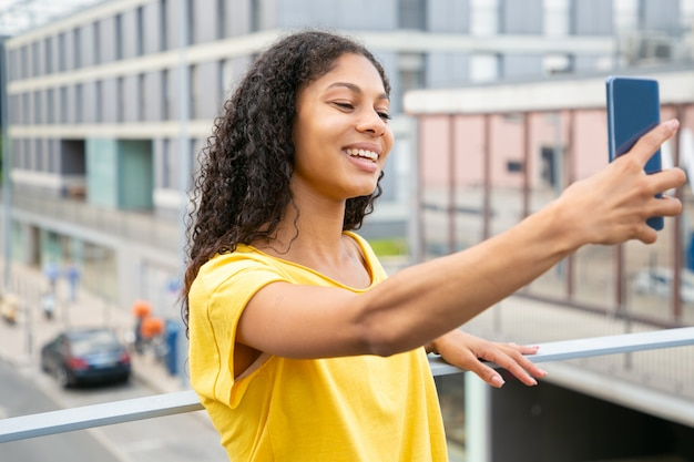Happy joyful latin girl taking selfie outside Free Photo