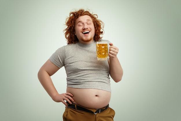 Felice gioioso giovane uomo in sovrappeso con la testa rossa riccia chiudendo gli occhi per il divertimento Foto Gratuite