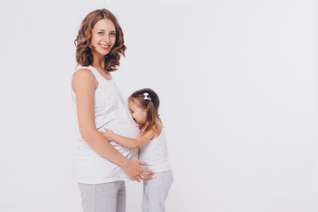 Happy kid girl hugging pregnant mother's belly, pregnancy and new life concept Premium Photo