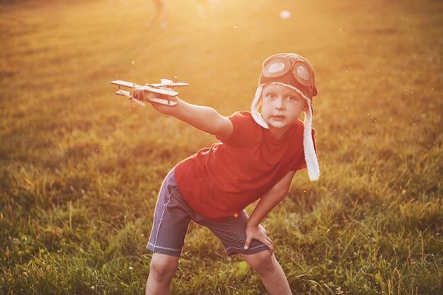 木のおもちゃの飛行機で遊んで飛行になることを夢見てパイロットヘルメットで喜んでいる子供 無料写真