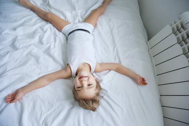 Happy kid laying in white bedroom. little boy play on the bed wearing pajamas at home Premium Photo
