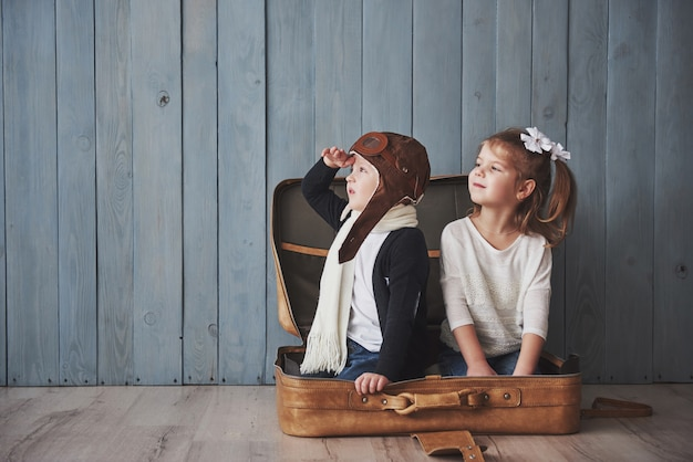 Happy kid in pilot hat and little girl playing with old suitcase. childhood. fantasy, imagination. travel Premium Photo