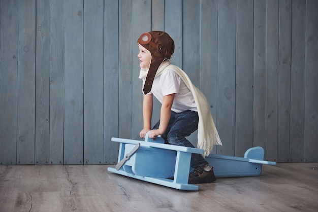 Happy kid in pilot hat playing with wooden airplane against. childhood. fantasy, imagination. holiday Premium Photo