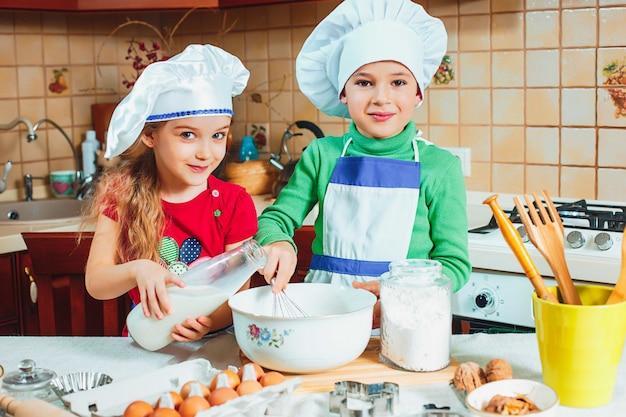 Happy kids are preparing the dough Free Photo