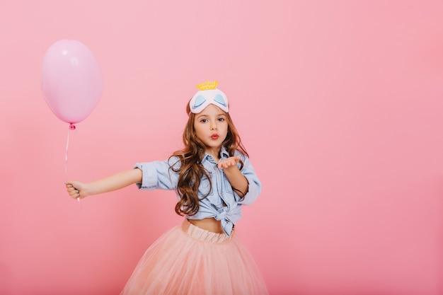 バルーンを押しながらピンクの背景に分離されたカメラにキスを送信する長いブルネットの髪を持つ驚くべき少女の幸せな子供カーニバル。チュールスカートを着て、頭にかわいいお姫様マスク 無料写真