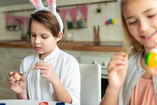 幸せな子供のイースターエッグを着色、イースターバスケットの準備 Premium写真