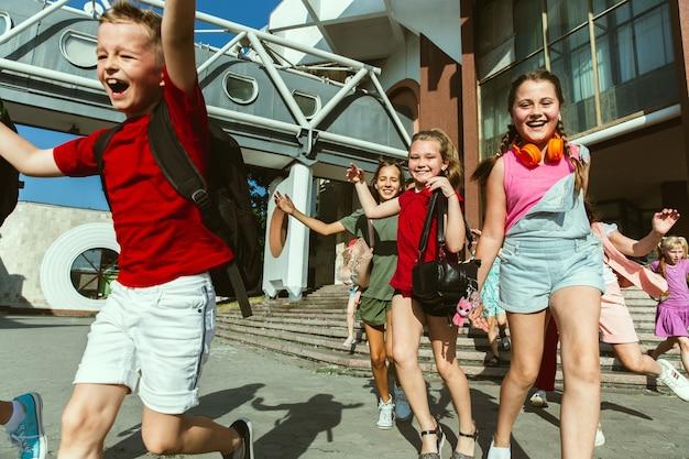 モダンな建物の前で晴れた夏の日に街の通りで遊んで幸せな子供たち。一緒に楽しんでいる幸せな子供やティーンエイジャーのグループ。友情、子供時代、夏、休日の概念。 無料写真