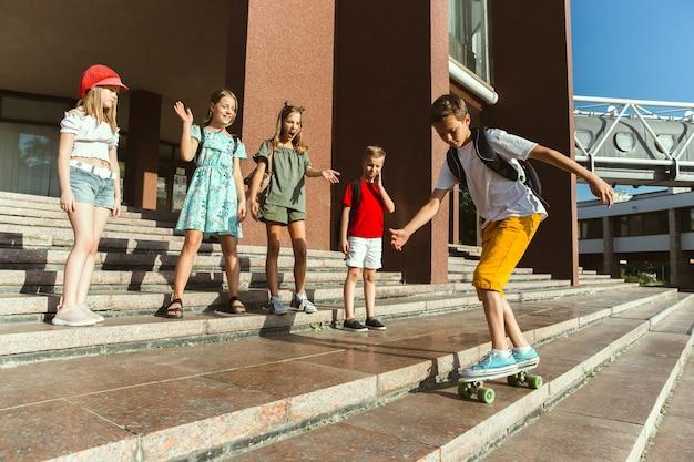 Счастливые дети, играющие на улице города в солнечный летний день перед современным зданием. группа счастливых детей или подростков, весело проводящих время вместе. понятие дружбы, детства, лета, праздников. Бесплатные Фотографии
