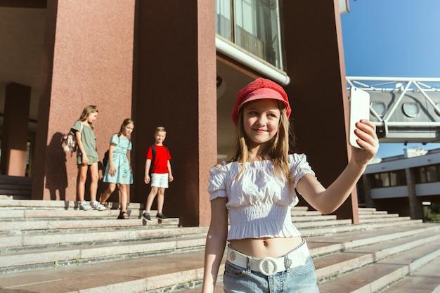 モダンな建物の前で晴れた夏の日に街の通りで遊ぶ幸せな子供たち 無料写真