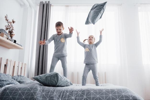 흰색 침실에서 행복한 아이들. 어린 소년과 소녀, 형제와 자매는 잠옷을 입고 침대에서 재생됩니다. 아기와 유아를위한 잠옷과 침구. 집에서 가족 무료 사진