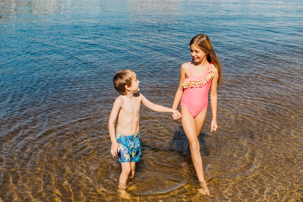 Happy kids standing in water on beach Free Photo