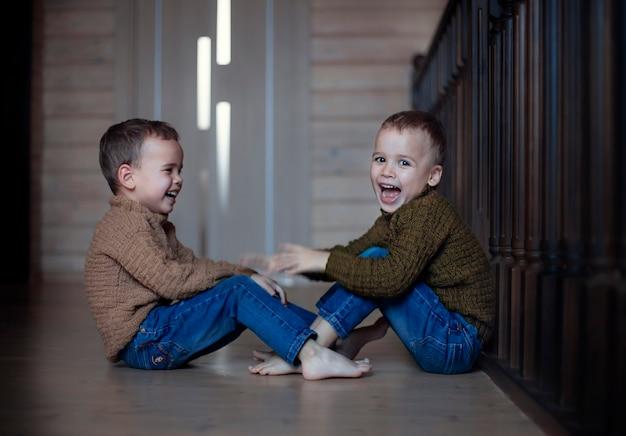 Счастливые дети братья-близнецы дома играют Premium Фотографии