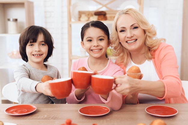 Happy kids with grandmother cheers cups with tea Premium Photo