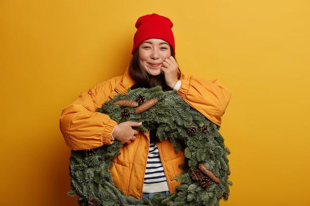 冬のアウターを着た幸せな韓国人女性は、誠実な感情を表現し、美しいトウヒの花輪を保持し、屋内の黄色の背景に立っています。 無料写真