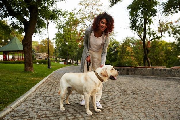 Счастливая леди, обнимая ее белая дружелюбная собака во время прогулки в парке Бесплатные Фотографии