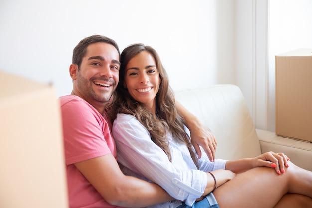 Felice coppia latina seduta sul divano tra scatole di cartone nella nuova casa, guardando la fotocamera, sorridendo, ridendo Foto Gratuite