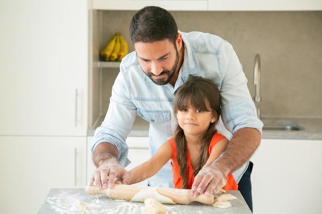 Felice ragazza latina e suo padre rotolare e impastare la pasta sul tavolo della cucina con farina in polvere. Foto Gratuite