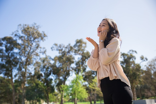 Happy laughing asian girl totally excited with phone talk Free Photo