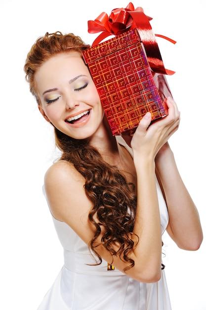 Счастливый смех милая девушка держит подарок закрывает голову над белой Бесплатные Фотографии