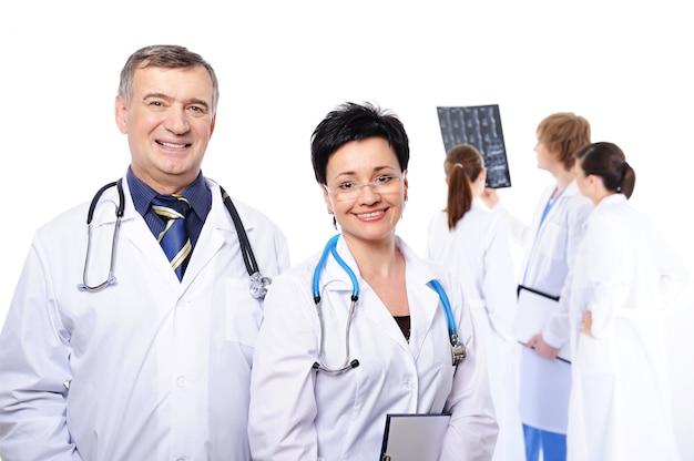 Medici che ridono felici in primo piano e tre medici che studiano i raggi x Foto Gratuite