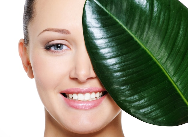 Happy laughing face of woman and large green leaf Free Photo