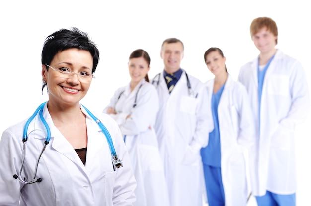 Счастливый смех женщина-врач на переднем плане и другие врачи Бесплатные Фотографии