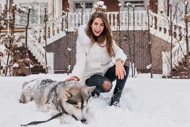 Счастливый смех женщина с прямыми волосами, сидя на снегу рядом со своей собакой. красивая женщина в джинсах и белой куртке позирует с хаски после прогулки зимним утром. Бесплатные Фотографии