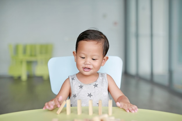 Happy little asian baby boy playing wood blocks tower game for brain and physical development skill in a classroom. focus at children face. kid imagination and learning concept. Premium Photo