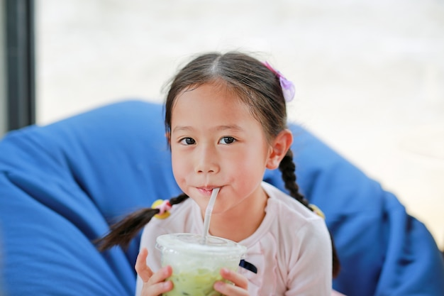 Happy little asian child girl drinking iced matcha green tea lying on sofa at cafe. Premium Photo