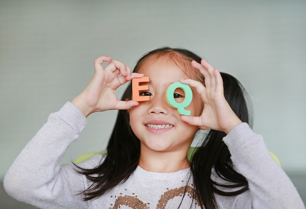 Happy little asian child girl holding alphabet letters on her face Premium Photo