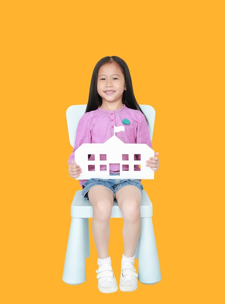 Happy little asian child girl holding paper school sitting on kid chair Premium Photo
