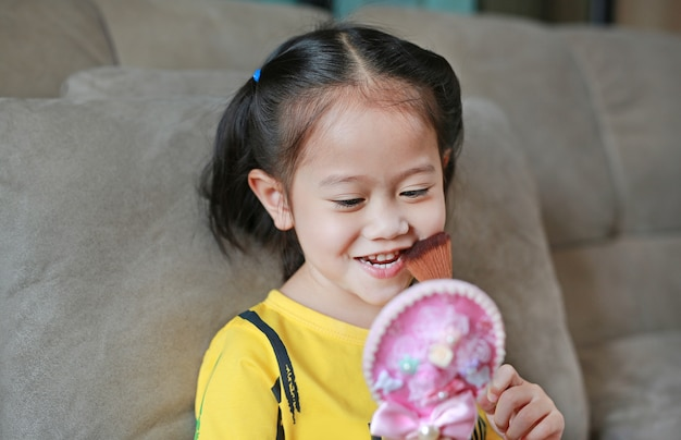 Happy little asian child girl with makeup and holding brush and mirror. Premium Photo