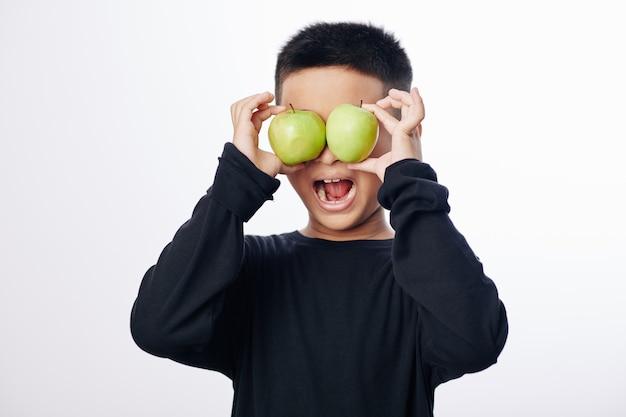 目の前で青リンゴを持って口を開けて幸せな小さなアジアの子供 Premium写真