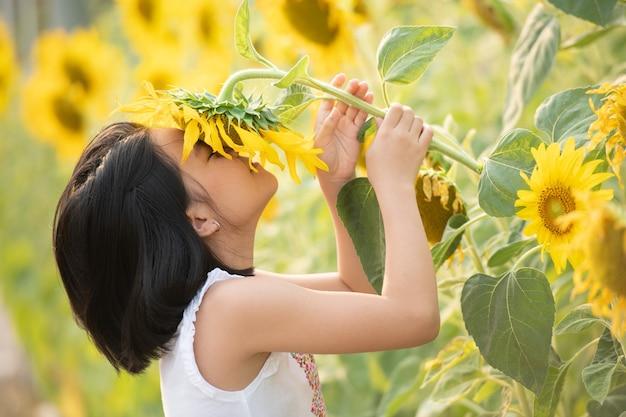 L'écologie expliquée aux enfants : une fille qui sent un tournesol