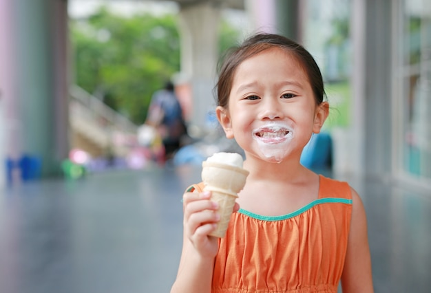 Happy little asian kid girl enjoy eating ice cream cone with stained around her mouth. Premium Photo