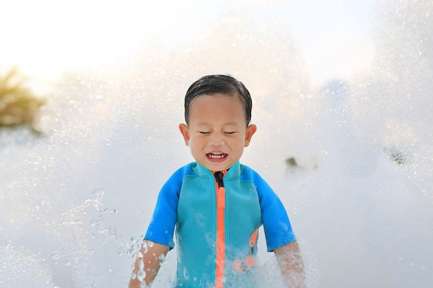 Happy little baby boy in swimming suit having fun in foam party at the pool Premium Photo